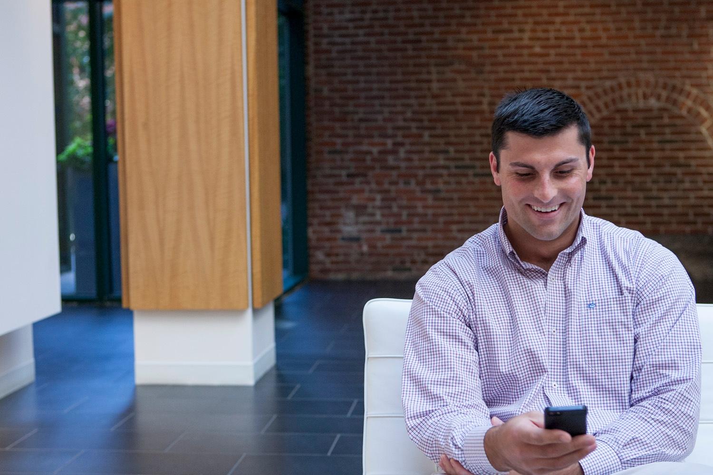 male looking at phone sitting smiling.jpg